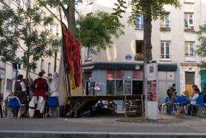 Posés place Sainte-Marthe, des chaises, une scène et des rideaux, derrière lesquels les comédiens se préparent. Paris, août 2010.