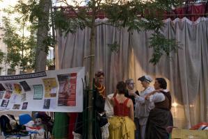 Vue des coulisses, derrière les rideaux à travers lesquels on distingue les lumières de la scène : à côté d'une banderole annonçant le programme du festival, les comédiens en costumes. Paris, août 2010.