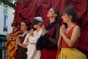 Cinq personnages alignés devant le rideau, les mains jointes en gestes de prière. Paris, août 2010.