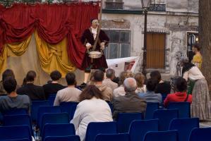 La jeune fille et la vieille femme sont passées dans le public et écoutent l'annonce d'un crieur public masqué, équipé d'un tambour. Paris, août 2010.