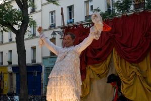 L'homme travesti vient d'ôter sa coiffure de femme et exulte, tandis qu'un autre personnage entre en scène. Paris, août 2010.