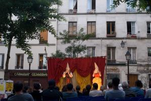 Vue plus large de la place, le public, la scène, où deux personnages enfilent des masques qui se prolongent en chapeaux pointus. Paris, août 2010.