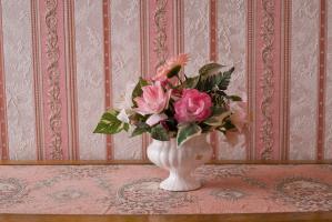 Bouquet de fleurs en plastique posé sur un meuble tapissé de rose, devant un papier peint de la même couleur. Nohant-en-Graçay, août 2009.