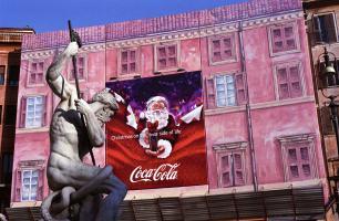 Piazza Navona, étalé sur la bâche en trompe-l'œil rose d'un échafaudage, le père Noël de Coca-Cola semble défier Neptune dans sa fontaine. Rome, décembre 2007.