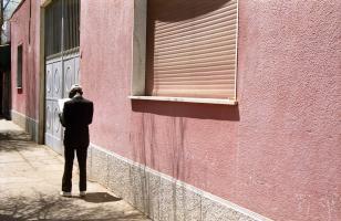 Un homme endimanché lit le journal en longeant un immeuble rose. Asmara, Erythrée, mars 2005.