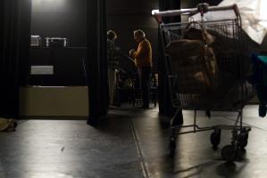 Vue de la scène avant la représentation, derrière un caddie de supermarché, deux comédiens se parlent en coulisses. Nanterre, octobre 2009.