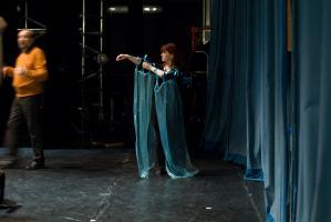La scène avant la représentation, les rideaux sont fermés, une comédienne arrange deux voiles bleus attachés à ses bras par des rubans, près d'un comédien en pull-over orange. Nanterre, octobre 2009.