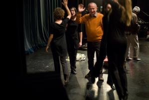 Avant la représentation, des comédiennes habillées de noir et un comédien en pull-over orange s'encouragent en se tapant les mains. Nanterre, octobre 2009.