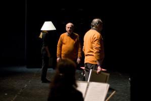 Derrière la silhouette d'une violoniste assise, les deux pères en pull-over orange et une choreute, en noir, avec un abat-jour sur la tête. Nanterre, octobre 2009.