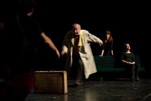 Le père en imperméable et le jeune homme se précipitent vers la valise. Au fond, une choreute assise sur un banc, une autre debout derrière. Nanterre, octobre 2009.