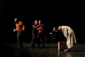 Entre le père en imperméable, plié au-dessus de sa valise, et le père épistolaire en pull-over orange en train de déclamer, deux choreutes dansent ensemble. Au fond, la violoniste. Nanterre, octobre 2009.