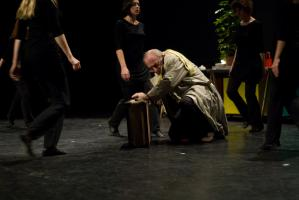 Le chœur se resserre autour du père en imperméable, accroupi près de sa valise dans une position de défense. Nanterre, octobre 2009.