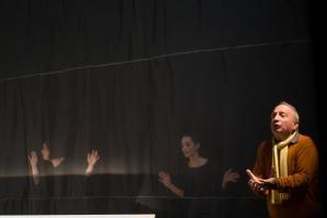 Le père, les mains jointes, les paumes ouvertes, devant un voile à travers lequel on aperçoit le chœur, comme en train de contempler des vitrines. Nanterre, octobre 2009.