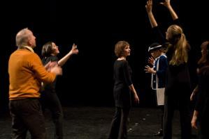 La pervenche, les mains levées en signe d'exaspération, entourée du père de dos et du chœur qui semblent chercher à attraper une balle. Nanterre, octobre 2009.