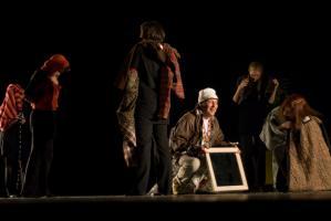 Accroupi parmi les choreutes qui déambulent vêtues de frippes, le clochard, l'air inspiré, tient un miroir. Nanterre, octobre 2009.