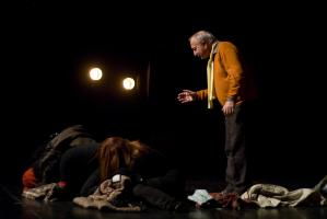 Le père, penché, parle au chœur recroquevillé au sol parmi les frippes. Nanterre, octobre 2009.