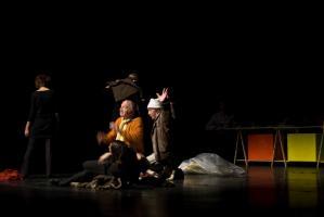 Le clochard, les bras levés, écartés, accroupi au sol à côté du père, près du chœur et des frippes. Au fond, la table à tréteaux et ses caisses rouge et jaune. Nanterre, octobre 2009.