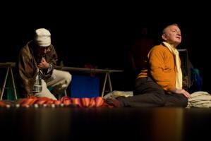 Le père, en pull-over orange, assis par terre parmi les frippes, et le clochard en train de s'asseoir, une main à terre, l'autre sur le cœur. Nanterre, octobre 2009.