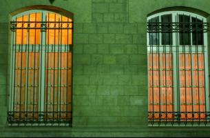Vers Denfert-Rochereau, deux fenêtres illuminées jaune orangé d'un immeuble de pierre à la façade verdâtre. Paris, printemps 2006.