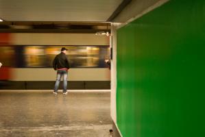 Sur le quai de RER à Nation, derrière le mur vert d'un couloir, un homme en jeans et casquette regarde passer un train. Paris, novembre 2009.