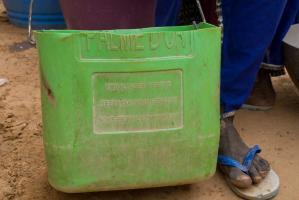 Près d'un pied chaussé d'une tong bleue et blanche, un seau vert fabriqué à partir d'un bidon en plastique qui annonce toujours : Emballages perdus. Réutilisation interdite sous peine de poursuite. Ndindy, Sénégal, janvier 2010.