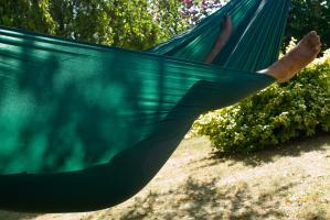 Deux pieds dépassent d'un hamac vert, à travers lequel on voit l'ombre du corps étendu. Triguères, août 2009.