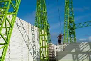 Debout sur des piles de barrières métalliques blanches, sur fond de ciel bleu, un homme s'appuie à la structure verte d'une grande roue foraine. Ténérife, Canaries, janvier 2010.
