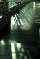 Ombres sur le sol brillant d'un couloir d'aéroport, la lumière entre verdie par les baies vitrées. Ténérife, Canaries, janvier 2010.