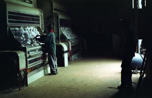 Dans un entrepôt, deux hautes machines, des égreneuses, font tomber du coton sur leurs tapis presque verticaux. Devant l'une d'elles, un homme semble trier les fleurs de coton. Kedougou, Sénégal, janvier 2008.