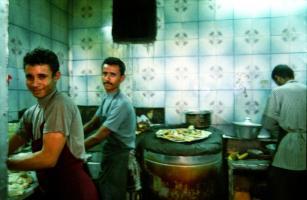 Dans la cuisine d'un restaurant aux murs carrelés de vert, deux hommes en tabliers travaillent de la pâte à pain. Sanaa, Yémen, janvier 2005.