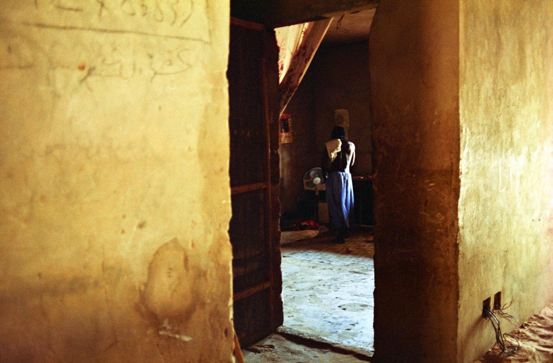 Aperçu par la porte ouverte, Modou, de dos, torse nu, au fond de sa chambre. Touba, Sénégal, février 2008.