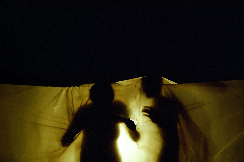 Saynète de la représentation de fin d'année du cours de théâtre du Centre de Formation et de Rééducation Professionnelle (CFRP) de l'AVH : deux silhouettes sous une bâche de plastique éclairée par-derrière. Paris, juin 2005.