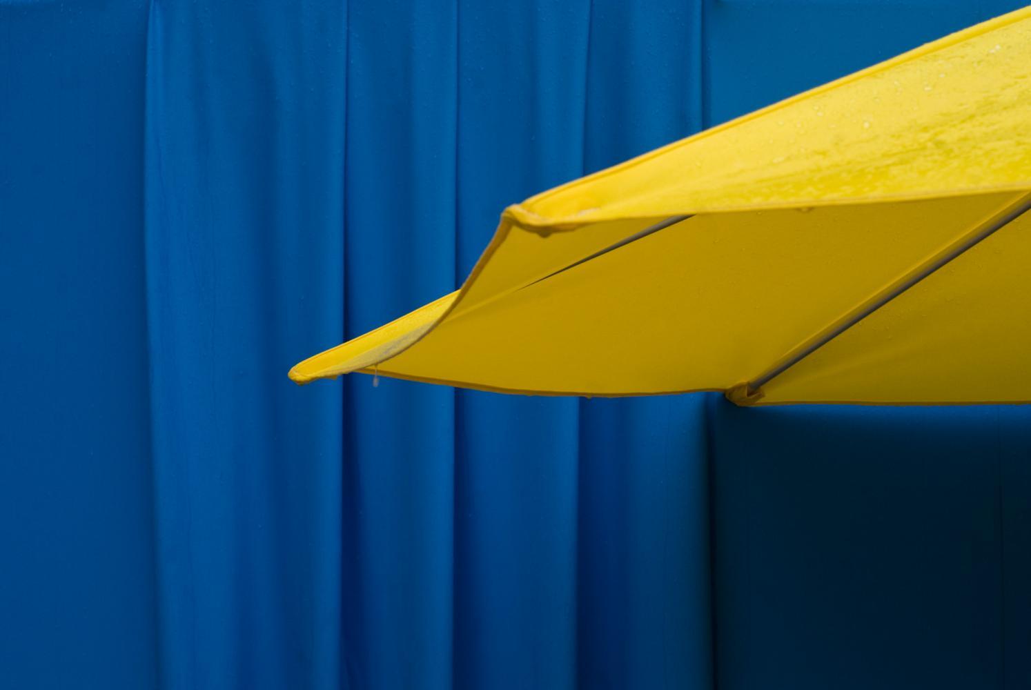 Parasol jaune devant une bâche bleu vif. Paris, août 2010.